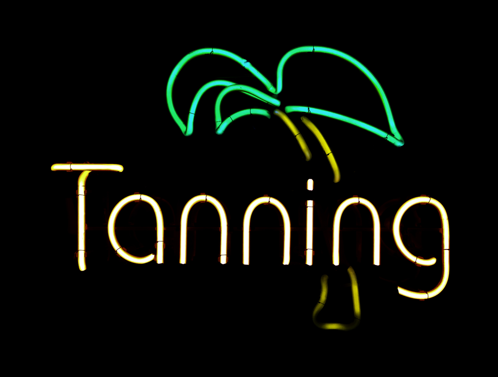 Neon sign in window of tanning salon, isolated on black
